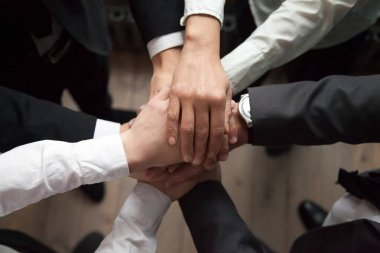 Motivated business people put hands together, trust and support