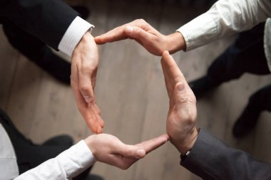 Business people join hands in circle, protection and support con