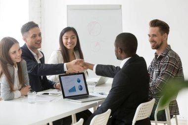 Satisfied multiracial businessmen handshaking after successful g
