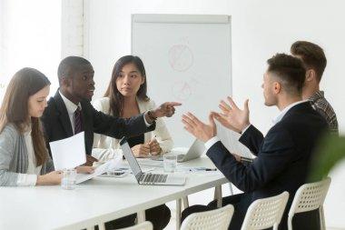 African worker disputing disagreeing with caucasian colleague du