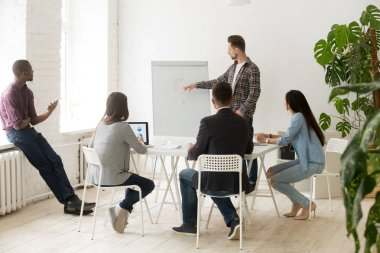 Serious casual businessman giving presentation to employees work