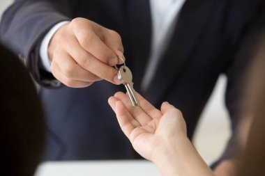 Female hand taking key from realtor buying renting new home