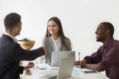 Smiling businesswoman shaking hand of male partner at group meet