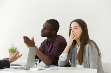 Tired bored businesswoman yawning at boring office meeting with diverse colleagues or partners, young lazy employee or dull intern showing bad manners, impolite behavior, suffering from lack of sleep