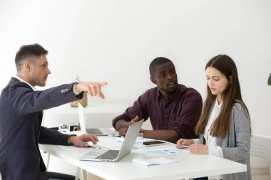 Rude multiracial businessmen humiliating firing female colleague