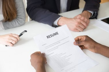 African-american applicant holding resume at job interview, clos