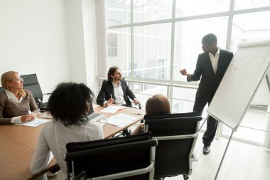 African business coach gives presentation for team at board meet