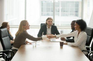 Diverse smiling businesswomen shaking hands greeting at multirac