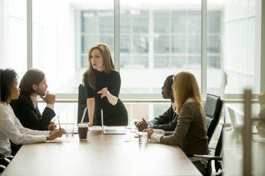 Serious woman boss talking to multiracial team at boardroom meet