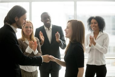 Smiling ceo handshaking successful female worker showing respect