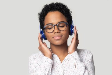 Head shot relaxed African American woman in headphones enjoying music