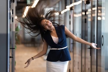 Funny Asian businesswoman dancing in empty hallway, celebrating success