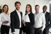 Portrait of happy diverse colleagues posing for picture in office
