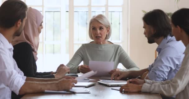 Mature corporate leader mentor holding document speaking at group meeting