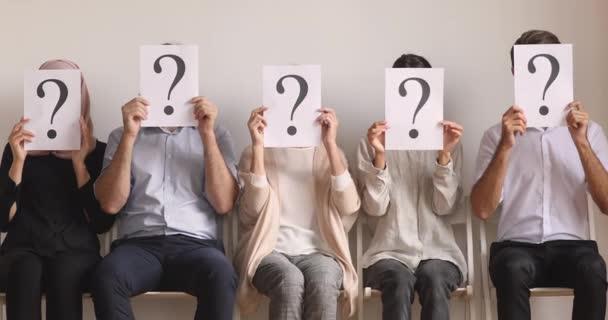 Állástalan álláskeresők ülnek sorban elrejtőzve a kérdésekkel.