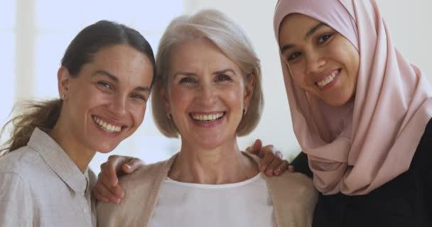 Tři různé usmívající se ženy přátelé objímající pohled na kameru