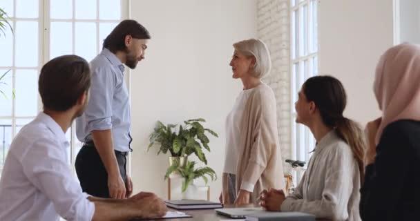 Happy older female employee get promoted rewarded handshaking boss