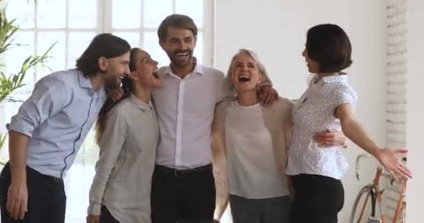 Excited multiethnic business people team embrace laugh celebrate corporate success