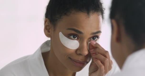 Šťastný africký žena s obličejem pásky oko při pohledu do zrcadla