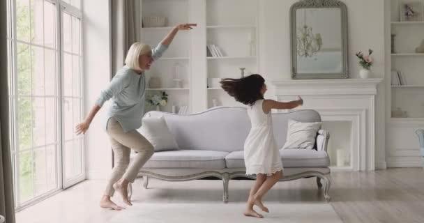Roztomilé dívka vnučka tanec s zralou babičkou v obývacím pokoji