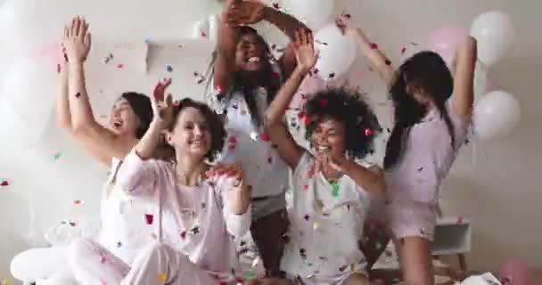 Šťastné vzrušené mladé dámy slaví pyžamový večírek v podzimních konfety