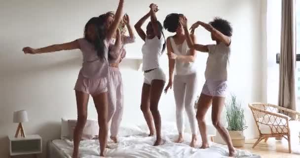 Őrült gyönyörű változatos fiatal lányok táncolnak szórakozás az ágyban