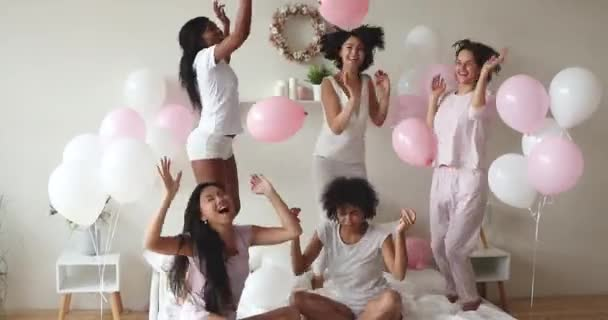 Excited sexy diverse ladies dancing on bed celebrate with balloons