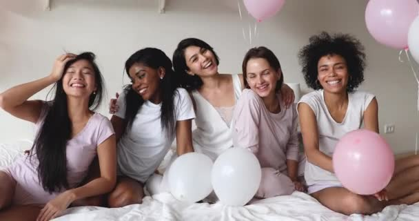 Carefree diverse ethnic girls bonding looking at camera on bed