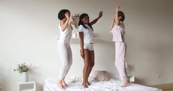 Három gondtalan, változatos hölgy álomruhát hord ugráló táncot az ágyon.