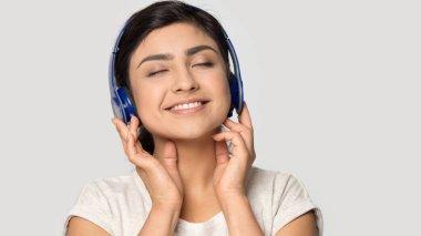 Smiling satisfied Indian girl in headphones enjoying favorite music