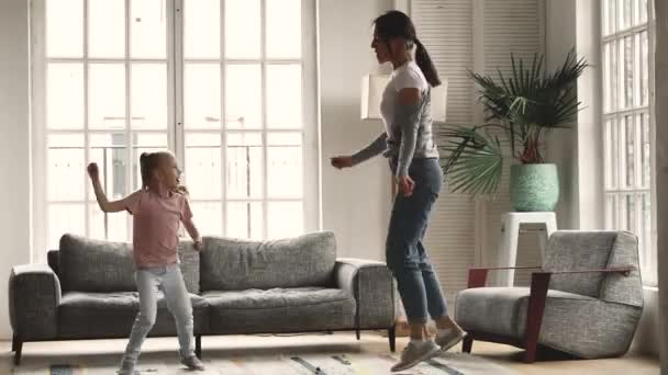 Funny young mum and child daughter having fun dancing together