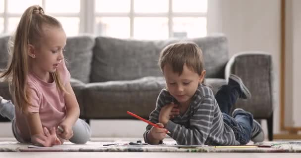 Two little kids coloring picture with pencils lying on floor