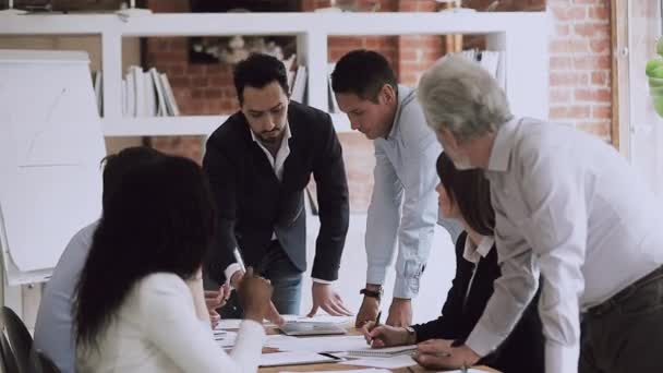 Young and old colleagues disputing on paperwork at corporate briefing