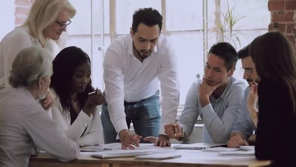 Diverse business team brainstorming on paperwork talking laughing at meeting