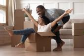 Afričanky šťastný manželka sedí uvnitř krabice manžel jezdí na ní