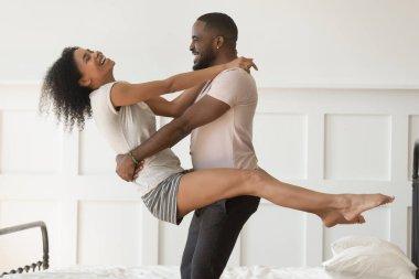 Happy biracial couple in pajamas dancing at home