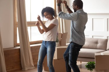 African couple celebrating moving at new home dancing near boxes