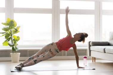 Fit millennial female doing side plank at home