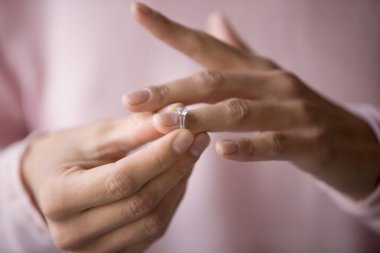 Close up of woman removing ring filing for divorce