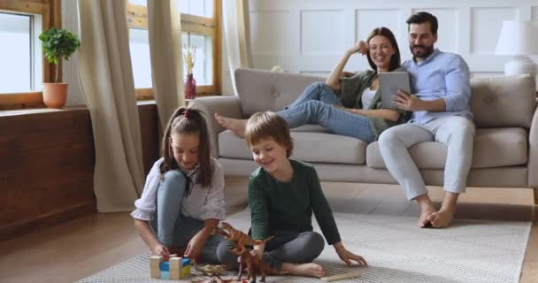 Happy parents with cute kids siblings lounge in living room
