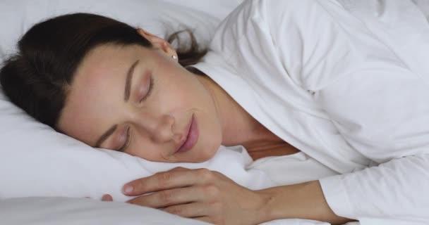 Klidná klidná mladá žena atraktivní tvář odpočívá v pohodlné posteli