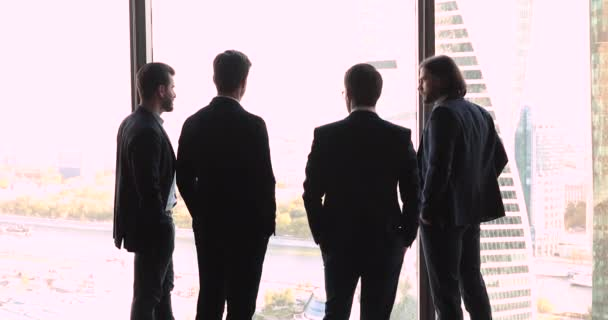Back view at successful businessmen looking through big office window