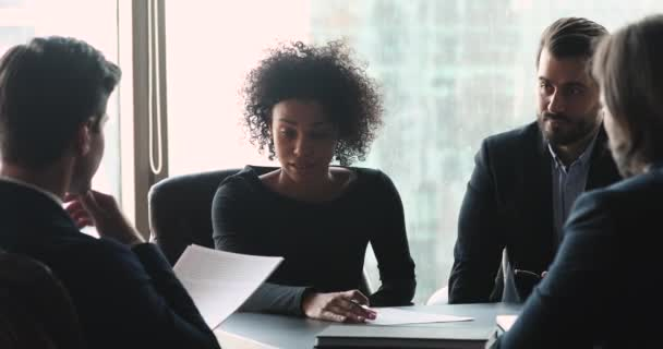 African female leader discussing contract at diverse group meeting table