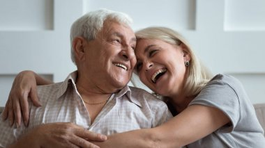Overjoyed middle aged woman cuddling happy older 80s father.