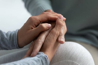 Close up image grown up daughter holding hand of mother
