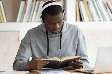 Concentrated african american guy reading book in earphones.