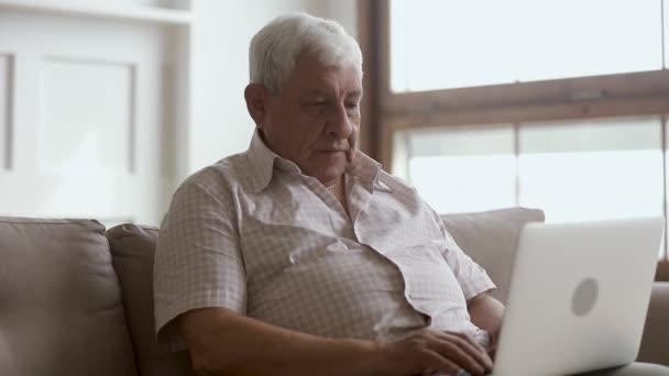 Senior older man using laptop sit on sofa at home