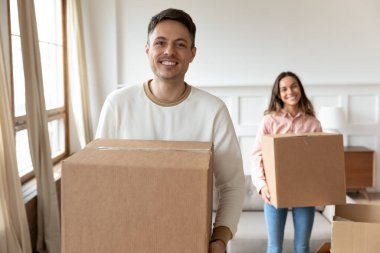 Happy man carrying box moving into new house with girlfriend