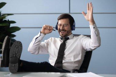 Happy millennial worker listen to music in headphones in office