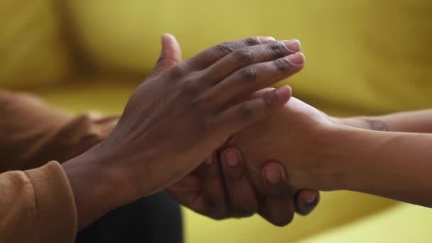 Freund eines schwarzen Mannes hält sanft streichelnde Hände einer afrikanischen Frau